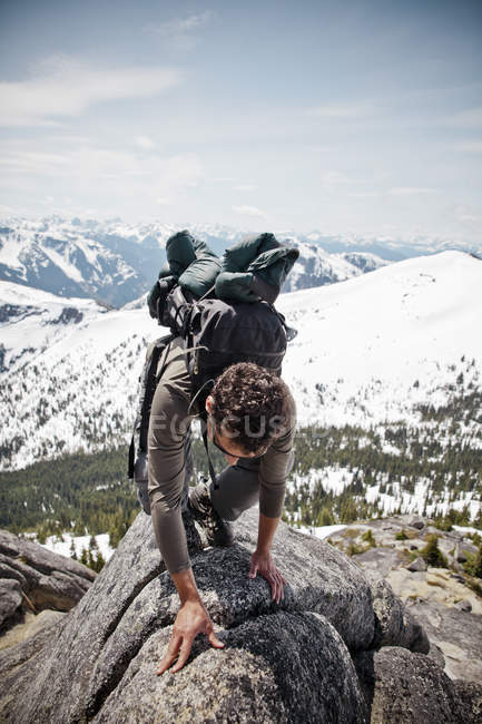 A backpacker scrambles over granite rock. — Stock Photo