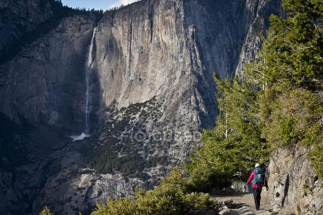 Backpacker marchant sur le sentier avec les chutes supérieures de Yosemite à l'arrière-plan, parc national de Yosemite, Etats-Unis — Photo de stock