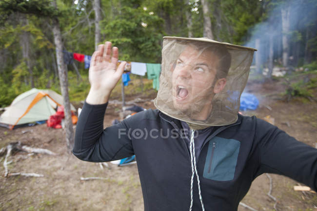 A man swats at mosquitoes while wearing a mosquito head net at his campsite. — Stock Photo