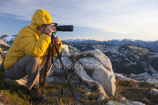 A photographer uses a tripod and a zoom lens to capture a landscape photo from the top of a rocky mountain ridge in British Columbia, Canada. — Stock Photo