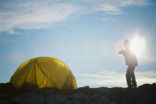 Silhouette of a photographer standing beside his tent shortly after sunrise. — стокове фото