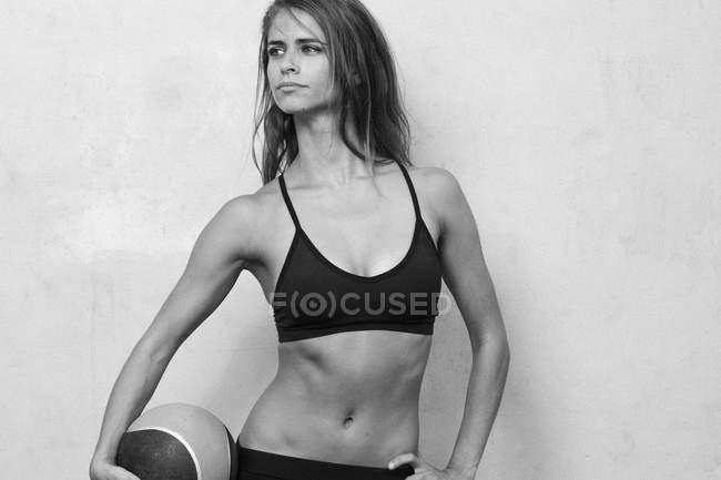 Fitness-Modell Maria Ambrose posiert mit einem gewichteten Ball vor dem Hintergrund der Zement in Brooklyn, New York. — Stockfoto