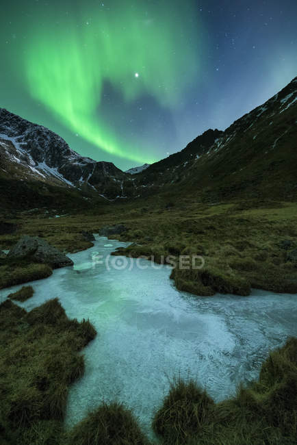 Aurora Boreal sobre gelo congelado rio e montanha paisagem, Flakstady, Ilhas Lofoten, Noruega — Fotografia de Stock