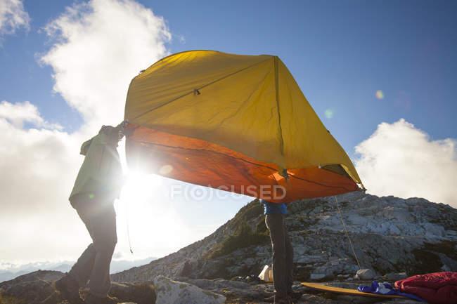 Un couple de routards lever leur tente dans l'air afin de le déplacer vers un emplacement de camping plus attrayant sur une crête rocheuse de montagne en Colombie-Britannique, Canada — Photo de stock
