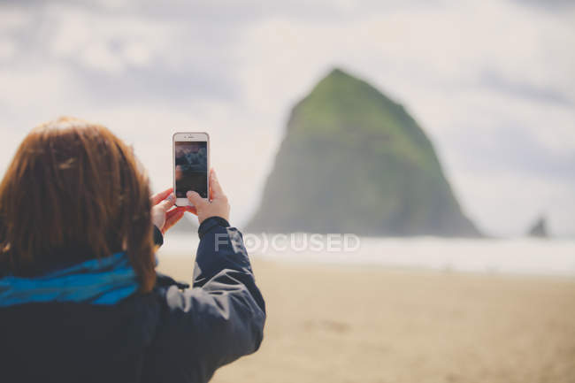 A young woman uses her smartphone to take a picture of Haystack Rock while visiting Cannon Beach, Oregon. — Stock Photo