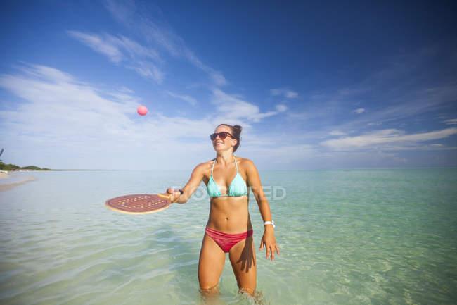 Молодая женщина играет с версией пляж Сквош, находясь в отпуске в Кайо Коко, Куба — стоковое фото