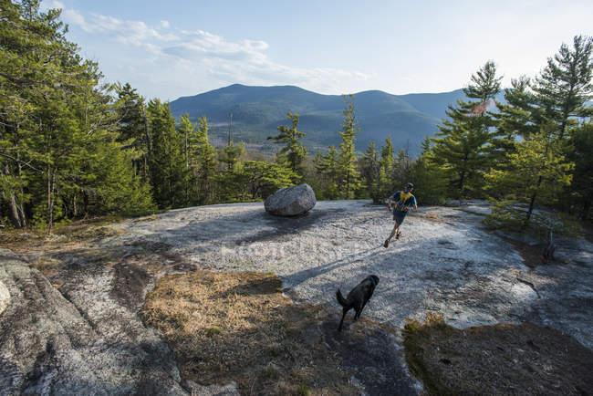 Mensch und Hund läuft durch Granitplatten in der Nähe von Whitehorse Felsvorsprung, Graben Bergen — Stockfoto