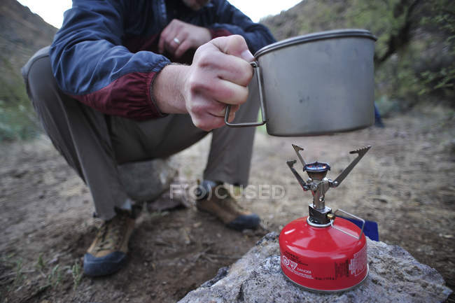 Man backpacker prepare dinner with a camp stove at camp close to Charleboise Springs in La Barge Canyon on the Dutchmans Trail in the Superstition Wilderness Area, Tonto National Forest near Phoenix, Arizona November 2011.  The trail links — стокове фото