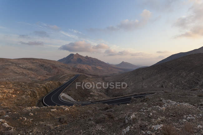 Empty windy road in a dramatic mountainous dry and desert landscape — Stock Photo