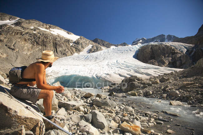 A hiker looks up toward Wedge Glacier as it melts in the mid day sun in Garibaldi Provincial Park. — Stock Photo