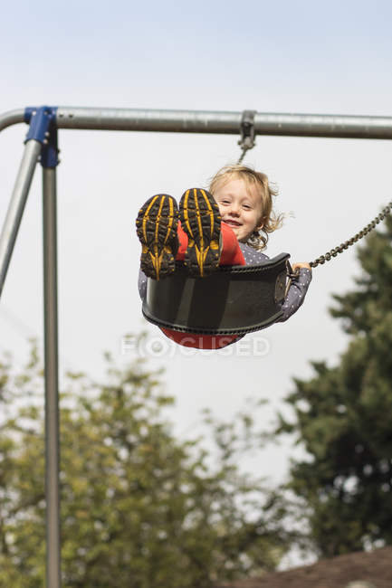 Smiling toddler girl swinging high at playground — Stock Photo