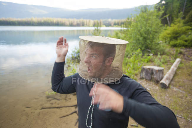 A man swats at mosquitoes while wearing a mosquito head net and camping outdoors. — Stock Photo