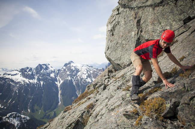 Uno scalatore attentamente attraversa una lastra di roccia ripida vicino alla sommità del picco di Trio, Columbia britannica, Canada. — Foto stock