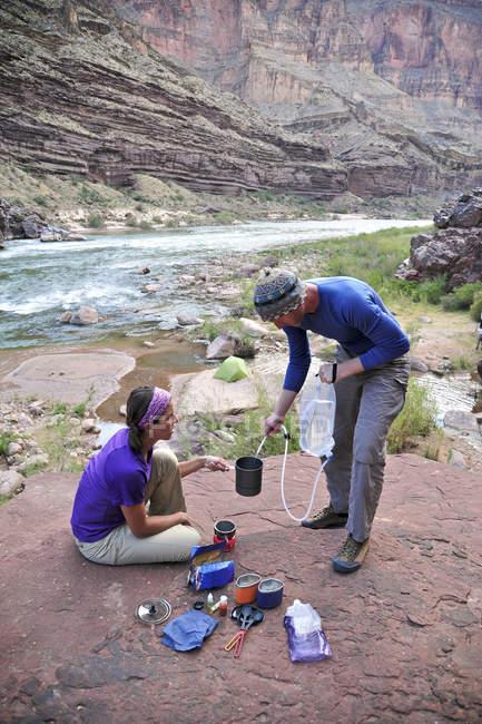 Gli escursionisti cucinare la cena su un patio scogliera-pizzicato sopra camp e il fiume Colorado vicino a Deer Creek Falls nel Grand Canyon di fuori di Fredonia, Arizona novembre 2011. Il ciclo di 21,4-mile inizia presso il sentiero di Bill Hall sul North Rim e scende 20 — Foto stock