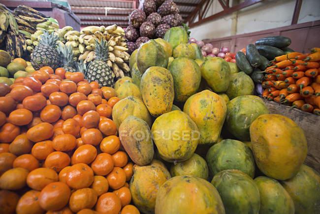 Laranjas, mamão, abacaxi, banana e variados produtos empilhados alta em um mercado — Fotografia de Stock