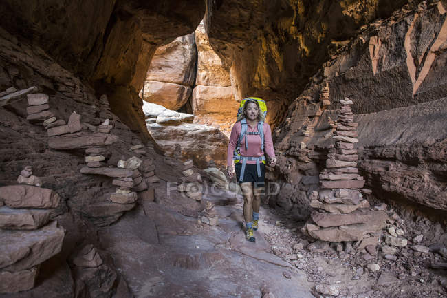 A woman backpacking past stone cairns on the Joint Trail in the Needles District of Canyonlands National Park, Monticello, Utah. — Stock Photo