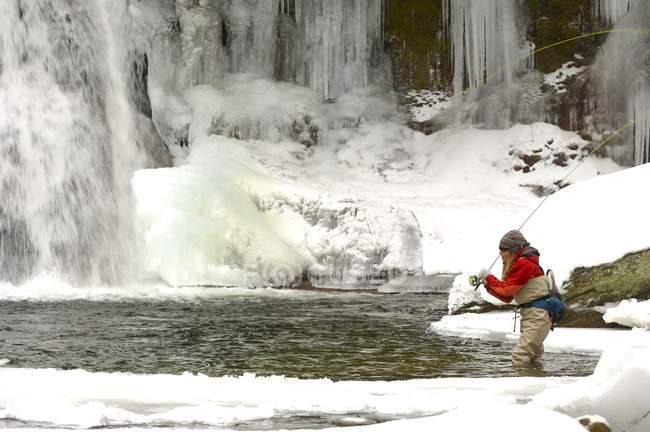 Жінка нахлистом проти водоспаду з бурульок — стокове фото