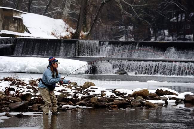 Pêche de mouche de femme dans le ruisseau froid d'hiver — Photo de stock