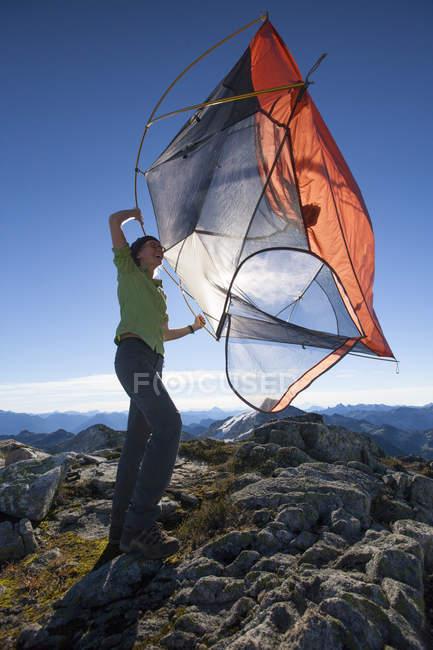 Un randonneur femme secoue la saleté hors de sa tente avant il emballer — Photo de stock