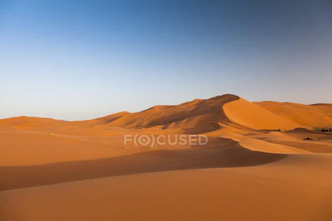 Sunrise on red sand dunes in Sahara desert at Erg Chebbi, Merzouga. Morocco — Stock Photo