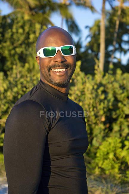 Спортивний людина в сонцезахисні окуляри, посміхаючись на камеру — стокове фото