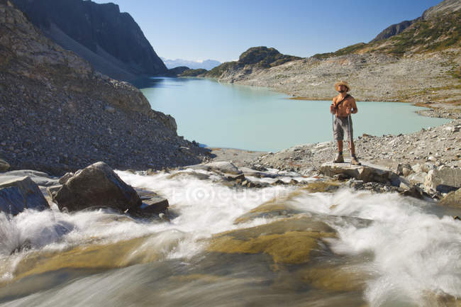 A shirtless hiker stands beside a river as it rushes into Wedgemount Lake  in Garibaldi Provincial Park. — Stock Photo