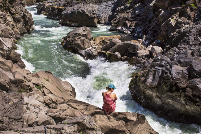 Rear view of woman sitting on rocks above river — Stock Photo