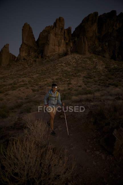Woman hikes at night by headlamp on the Treasure Loop Trail in Lost Dutchman State Park near Phoenix, Arizona November 2011.  The camp overlooks the spires of the Superstition Mountains. — Stock Photo