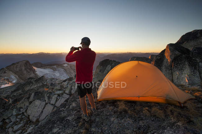 Hiker taking photo while camping on summit of Saxifrage Peak, Pemberton, Canada. — Stock Photo