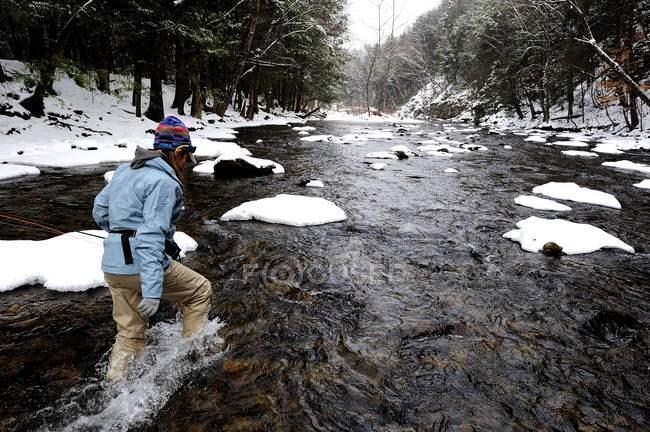 Femme pataugeant dans le ruisseau tout en pêchant à la mouche à l'hiver — Photo de stock
