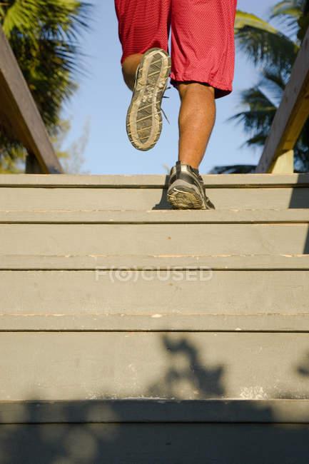 Человек на ноги, как он бежит вверх по лестнице открытый дощатый, тропической обстановке — стоковое фото