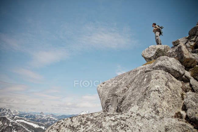 Un randonneur se dresse sur un tas de rocher de granit près du sommet du pic de l'aiguille. — Photo de stock