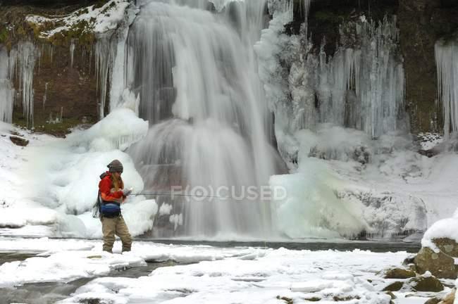Жінка літати риболовля на крик з заморожений водоспад у фоновому режимі — стокове фото