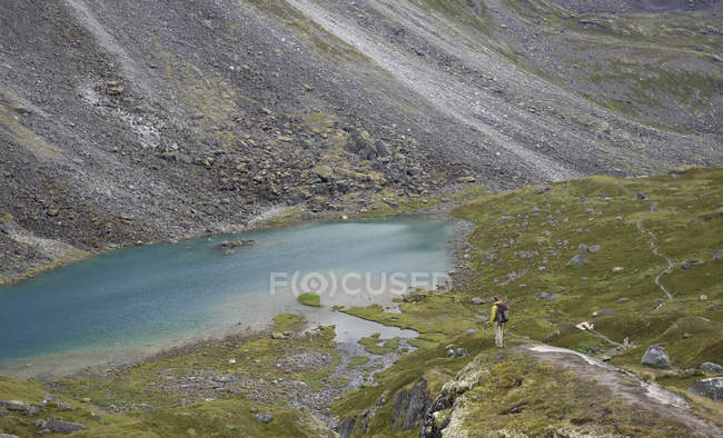 Woman hiker overlooks an alpine lake during a backpacking trip to Reed Lakes in the Talkeetna Mountains near Palmer, Alaska August 2011. — Stock Photo
