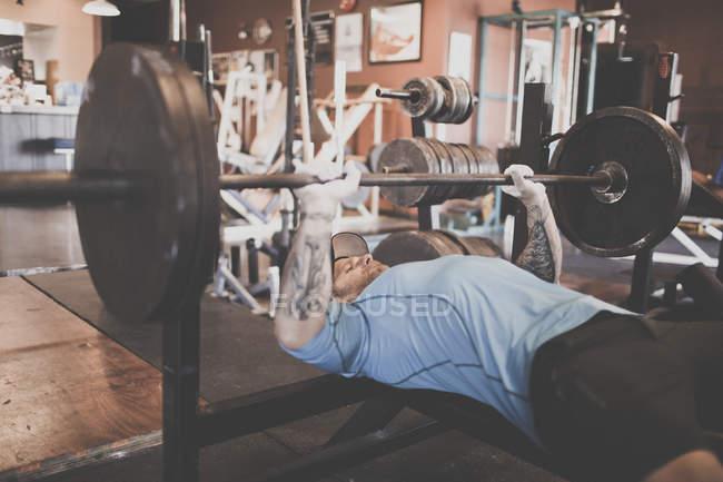 Adam Palmer, ein Berg-Athlet, hebt Gewichte beim Bankdrücken — Stockfoto