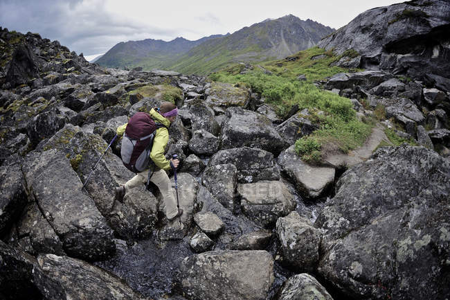 Woman hiker navigates a boulder field during a backpacking trip to Reed Lakes in the Talkeetna Mountains near Palmer, Alaska August 2011. — Stock Photo
