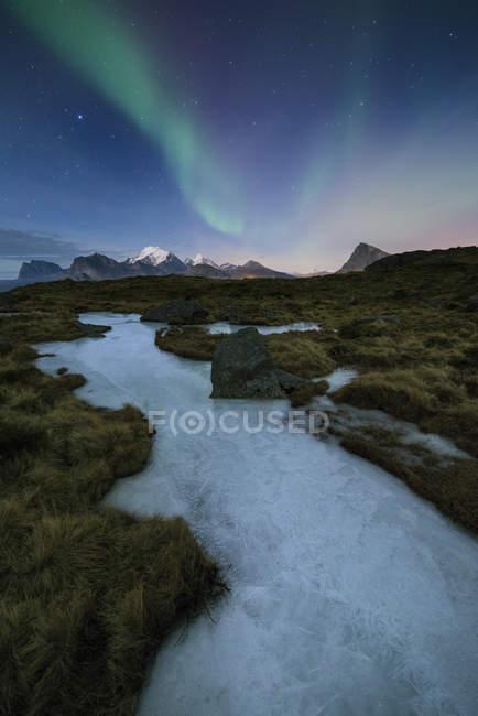 Aurora Borealis over frozen ice river and mountain landscape, Flakstady, Lofoten Islands, Norway — Stock Photo