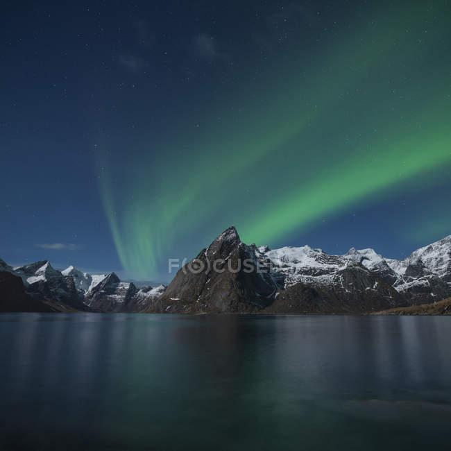 Aurora Boreal sobre o pico da montanha de Olstind, Hamny, perto de Reine, Moskenesy, Ilhas Lofoten, Noruega — Fotografia de Stock