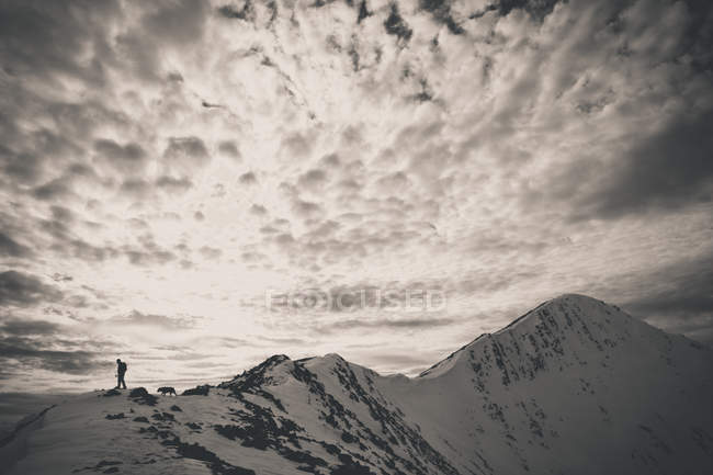 A backpacker and his dog hike a rocky ridgeline toward the summit of Frosty Mountain in the North Cascade Mountain Range. — Stock Photo