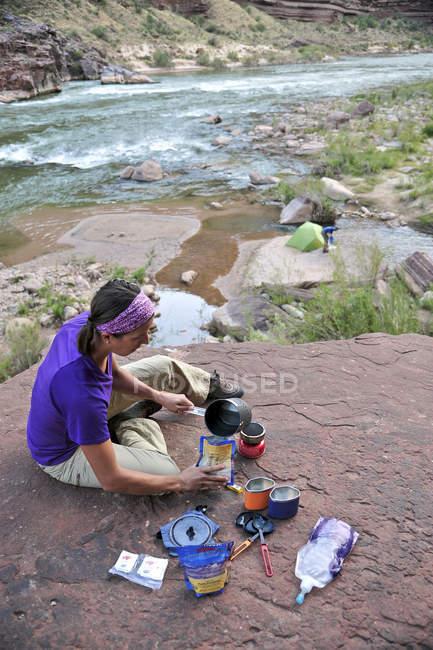 Weibliche Wanderer kocht Abendessen auf einer Klippe eingeklemmt Terrasse über dem Lager und den Colorado River in der Nähe von Deer Creek Falls im Grand Canyon außerhalb Fredonia, Arizona im November 2011. Die 21,4-Meile Schleife beginnt bei der Bill Hall Trailhead am North Rim und desc — Stockfoto
