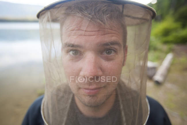 Portrait of a man wearing a mosquito head net while camping outdoors. — Stock Photo