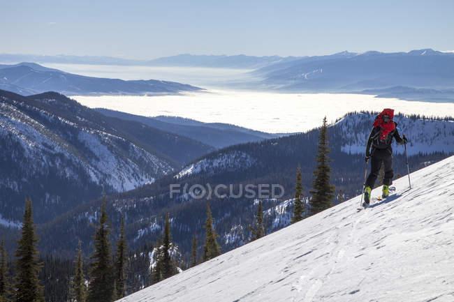 Backcountry Skifahrer zu Fuß durch Klapperschlange Berge hoch über eine Inversion im Bitterroot und Tal Missoula, Montana — Stockfoto