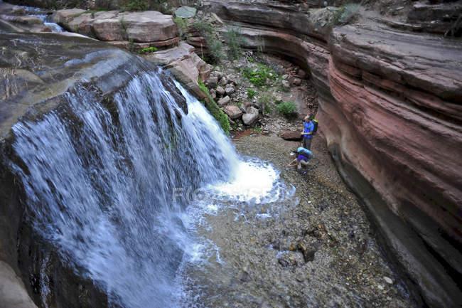 Wanderer vorbei an kleinen Wasserfällen entlang Deer Creek Narrows in den Grand Canyon außerhalb Fredonia, Arizona November 2011. Die 21,4-Meile Schleife beginnt bei der Bill Hall Trailhead am North Rim und senkt sich 2000-Füße in 2,5 Meilen durch Coconino Sandstø — Stockfoto