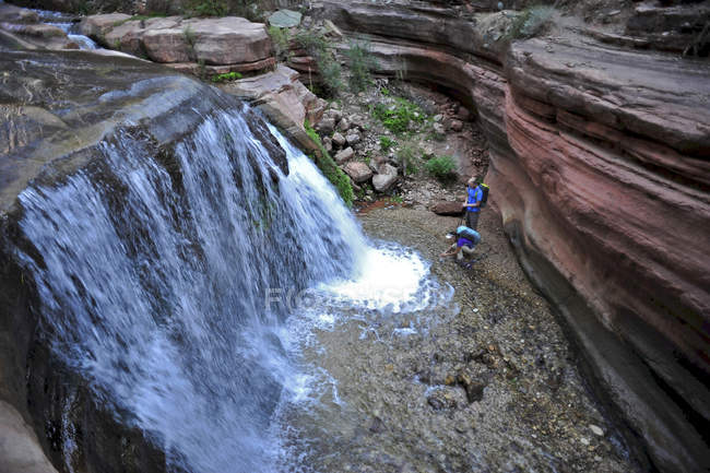Hikers past small waterfalls along  Deer Creek Narrows in the Grand Canyon outside of Fredonia, Arizona November 2011.  The 21.4-mile loop starts at the Bill Hall trailhead on the North Rim and descends 2000-feet in 2.5-miles through Coconino Sandsto — Stock Photo
