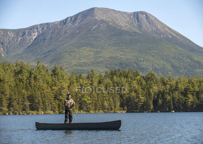 Fly fisherman in a canoe on Kidney Pond with Mt. Katahdin in the background. — Stock Photo