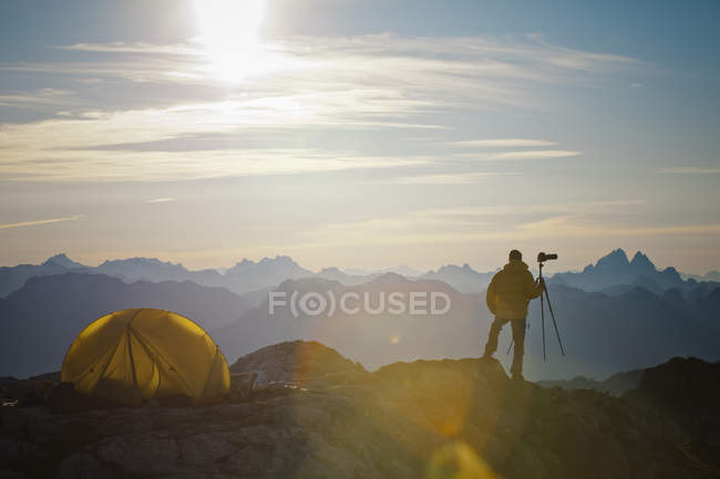 A photographer enjoys the view from his campsite on a rocky mountain ridge in Pinecone Burke Provincial Park, British Columbia, Canada. — стокове фото