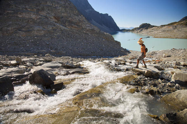 A shirtless hiker attempts to spear fish out of a river with a trekking pole in the Wedgemount Lake area of Garibaldi Provincial Park. — Stock Photo