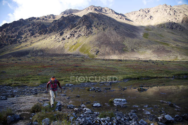 Female hiker crosses the North Fork Campbell Creek below Long Lake in the Chugach Mountains north of Anchorage, Alaska August 2011. — Stock Photo