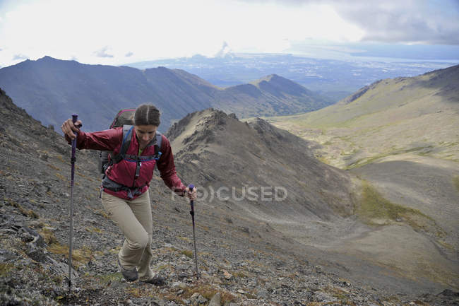 Female hiker starts her ascent up Tikishla Peak (5230-feet) with Anchorage and Knoya Peak in the distance of the Snowhawk Valley of the Chugach Mountains north of Anchorage, Alaska August 2011.  Even though the Snowhawk Valley is home to 5 of 12 peak — Stock Photo