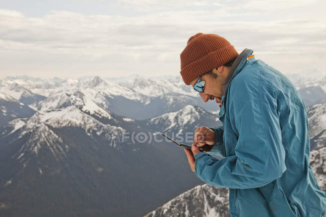 A hiker checks his text messages while standing on the summit of a mountain. — Stock Photo